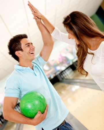 active date ideas bowling couple giving a high five