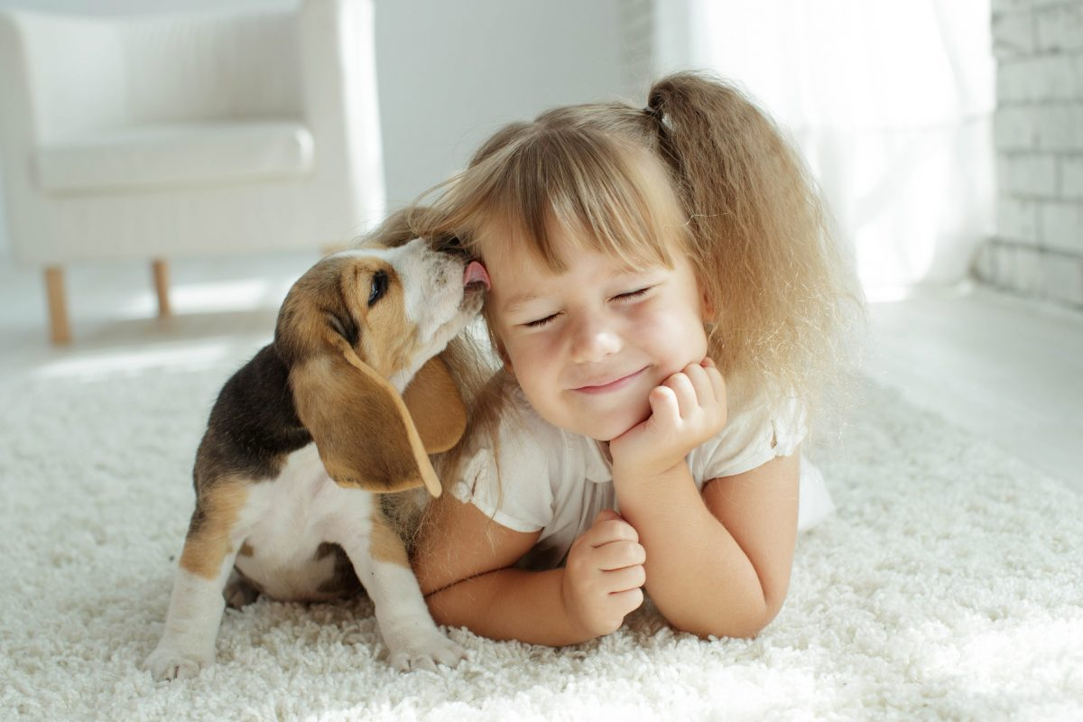 Girl with dog licking her face