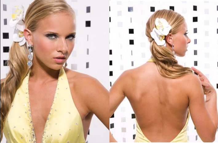 Low ponytail with big loose curls and big flower pin to complement the prom