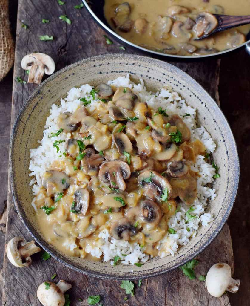 Mushroom stroganoff served on a bed of white rice in a deep plate.