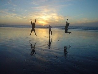 Three people jumping for joy on a beach with a sunset in the background