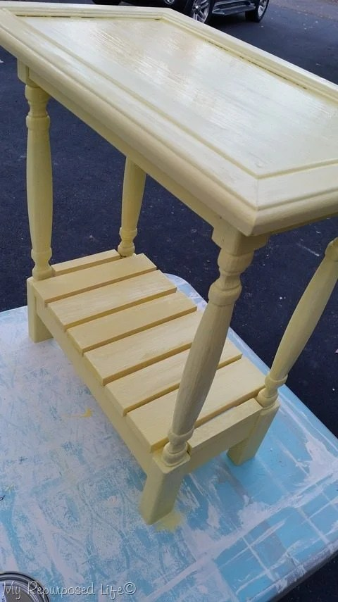 small yellow side table made out of a cabinet door, spindles and scrap wood