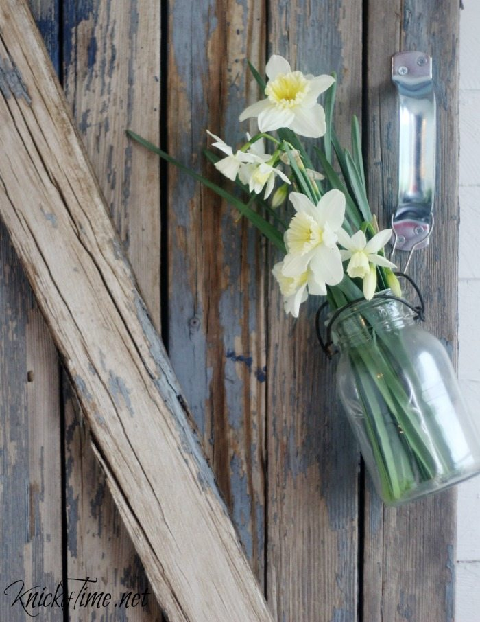 flowers in mason jar on barn gate