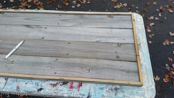 framing a rustic sign with fence boards