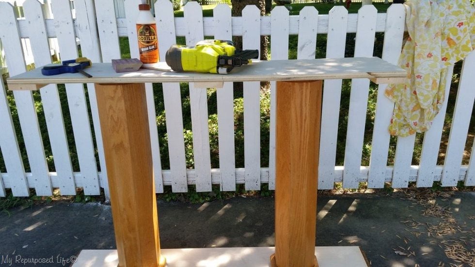 add scrap lumber to secure table top trim