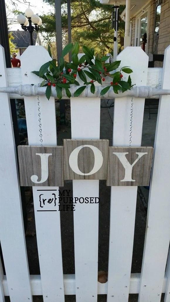 Joy spindle sign hanging on picket gate