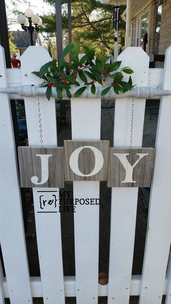 Joy spindle sign hanging on picket gate
