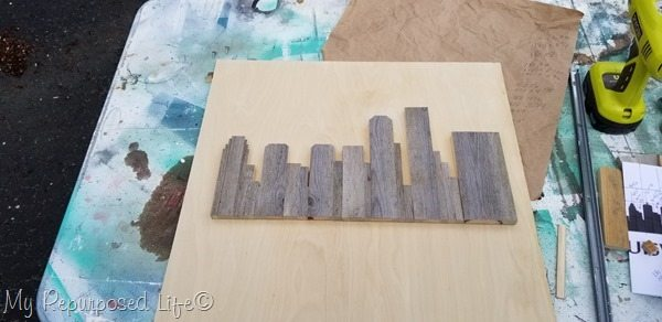 rustic skyline artwork placed on plywood