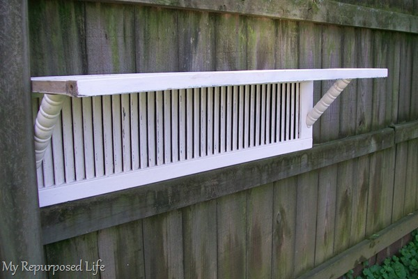 plant shelf hanging on fence