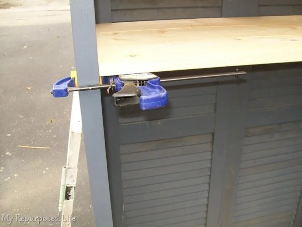 how to use a quick clamp to support a shelf during installation