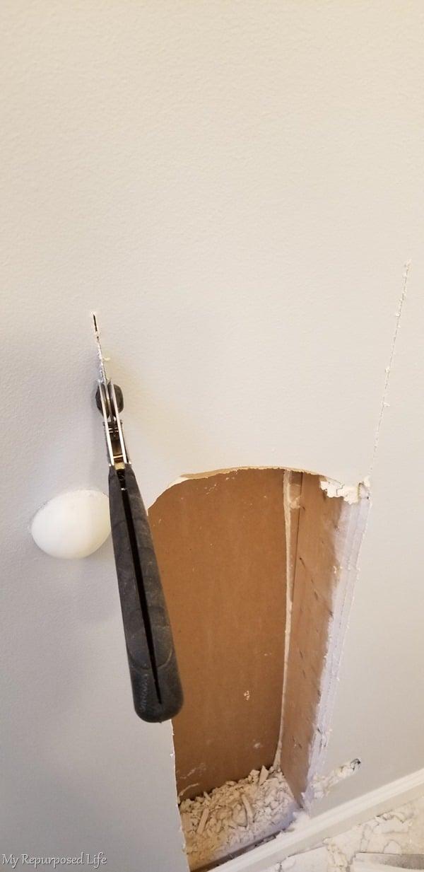 cutting drywall with handsaw