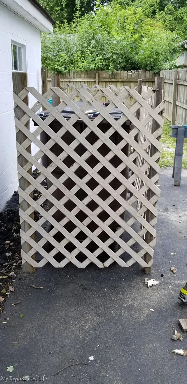 side view of garbage can enclosure made of lattice