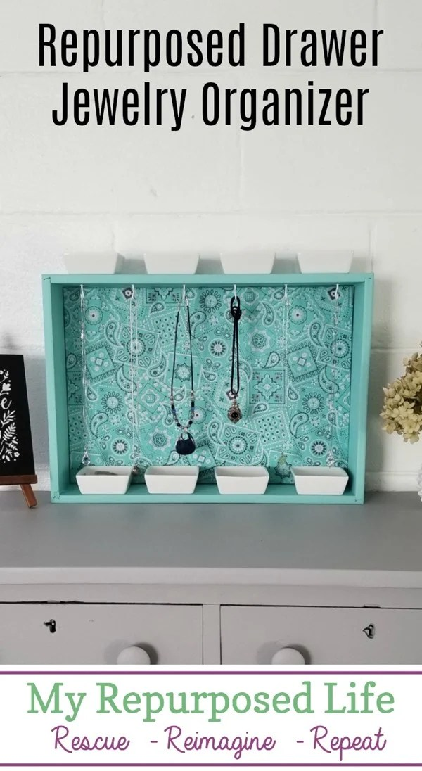 How to make your own repurposed drawer jewelry organizer. I used an old drawer, but you could easily customize this project by making a box out of 1x4's. This jewelry organizer can hang on the wall or rest on a dresser. The small white dishes are perfect for holding smaller items such as earrings or bracelets. #MyRepurposedLife #repurposed #furniture #drawer #jewelry #organizer #diy #project via @repurposedlife