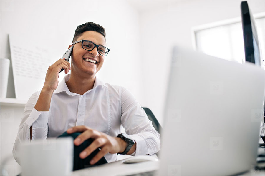 Man sitting at desk on phone