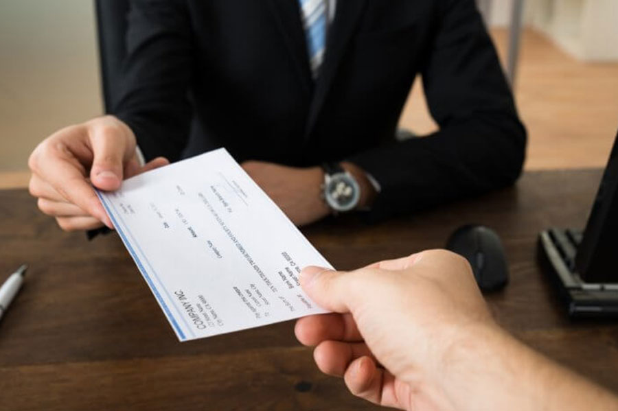 Person handing another person a check