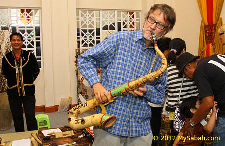 tourist playing bamboo saxophone