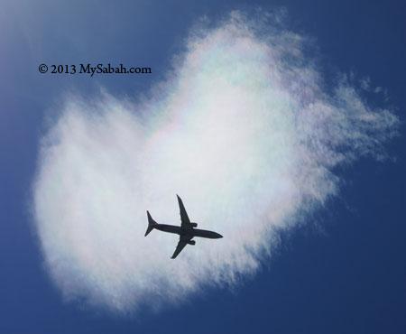 plane fly across color cloud
