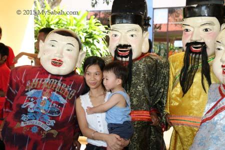 taking photo with big head Buddha and God of Wealth