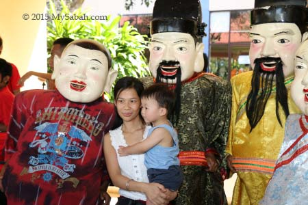taking photo with big head Buddha and God of Wealth