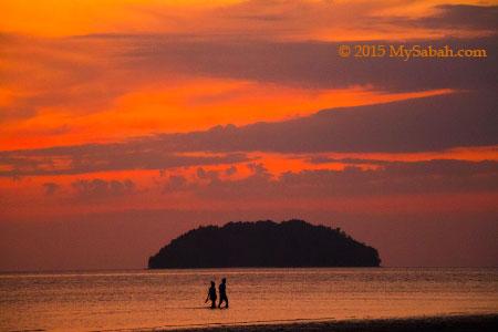 couples walking in sunset of Tanjung Aru Beach