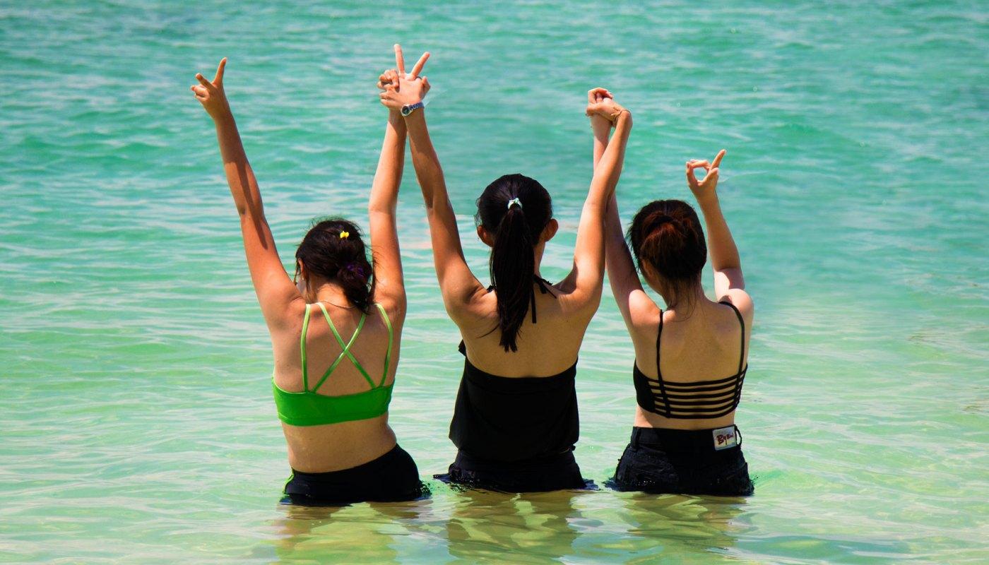 Three girls taking photo in the sea