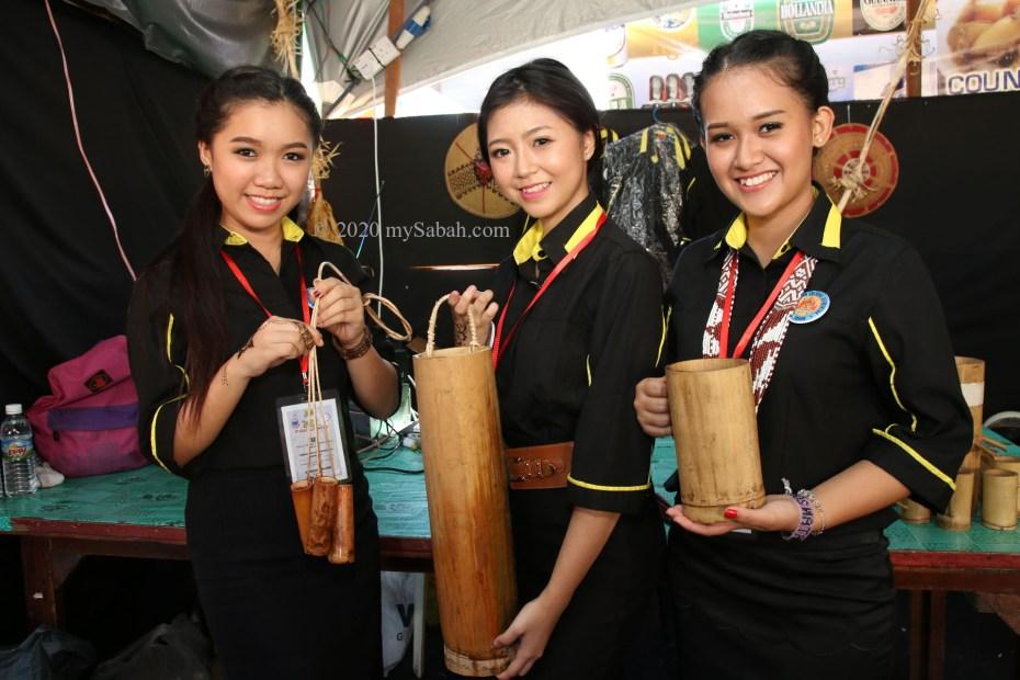 Girls holding bamboo cup (suki) for Sabah rice wine