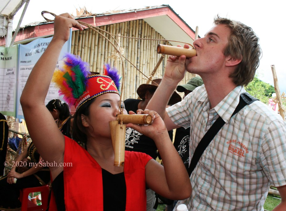 Tourist drinking tapai from small bamboo cup