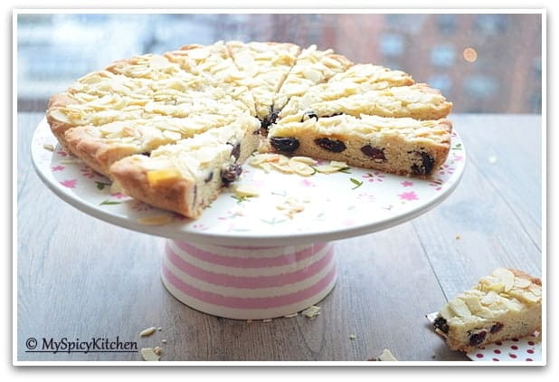 horizontal pic of cranberry almond sugar cookie wedges on a cake stand