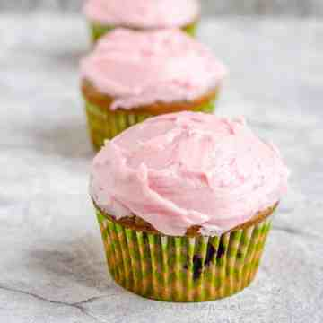 Blackberry cupcakes frosted with lime cream cheese arranged in a line. Focus is on the first cupcake.