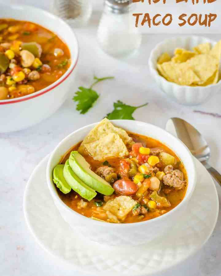 Bow of ground lamb taco soup garnished with avocado, sour cream and tortilla chips