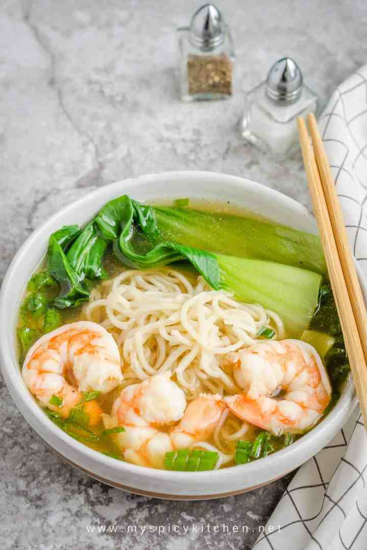 A bowl of shrimp noodle soup with chop sticks on the bowl