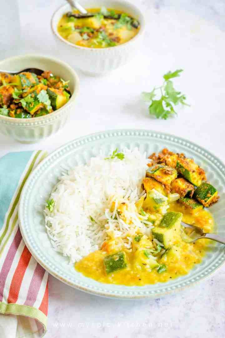 A plate of rice with zucchini pappu and zucchini stir fry.  Also in the frame are bowls of zucchini dal and zucchini stir fry.