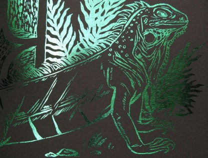 Detail of a foil print showing an iguana and the foil catching the light and looking green