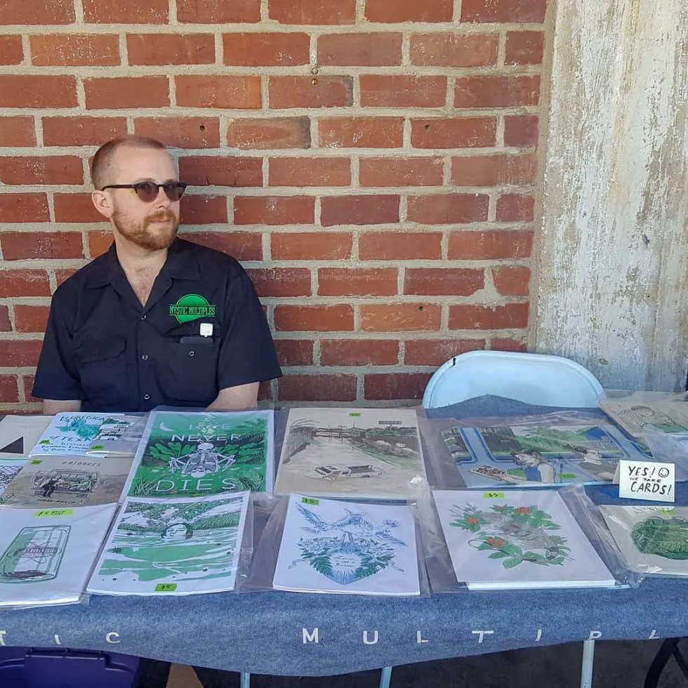 Photo of Mystic Multiples founder James sitting at a table selling prints