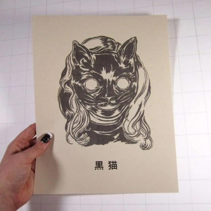 Risograph art print Kuro Neko with black ink on brown paper showing someone with long hair wearing a black cat mask