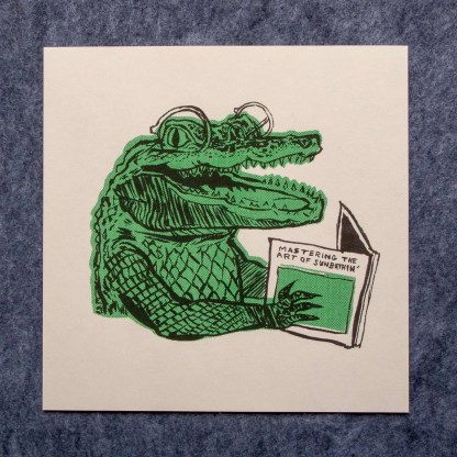 "Risograph art print with an illustration of an alligator smiling while reading a book titled ""Mastering the art of sunbathing"""
