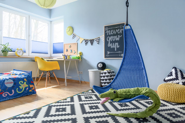A childs playroom or bedroom with a chair, rung and desk in it