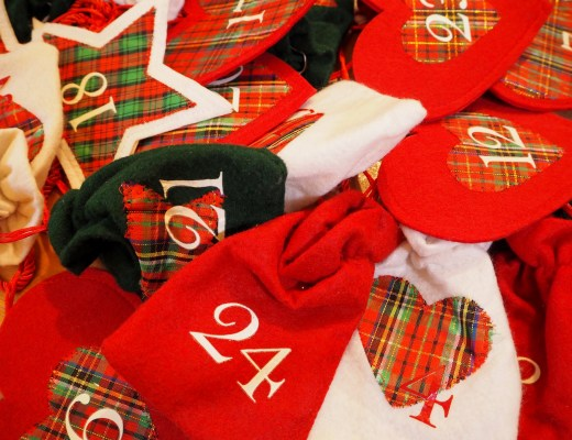 A pile of numbered Advent Calendar Gift Bags, Red, White and Black in colour