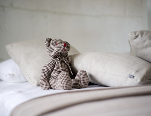 A bed with grey bedding and a grey teddy sat next to the pillows