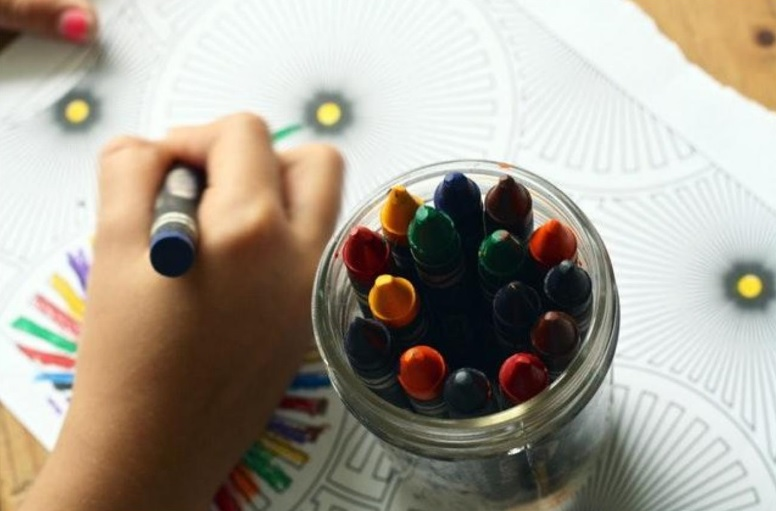 a girl colouring in a pattern with a pot of crayons
