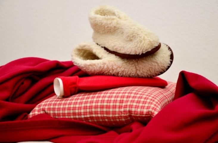 A pile of Red blankets, cushions, a hot water bottle and some cream slipper boots
