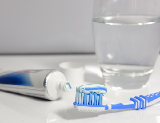 opened tube of toothpaste, a toothbrush with toothpaste on it and a glass of water - items needed for good oral health