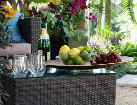 Rattan garden furniture, a sofa and table with a bottle of wine and fruit in a bowl