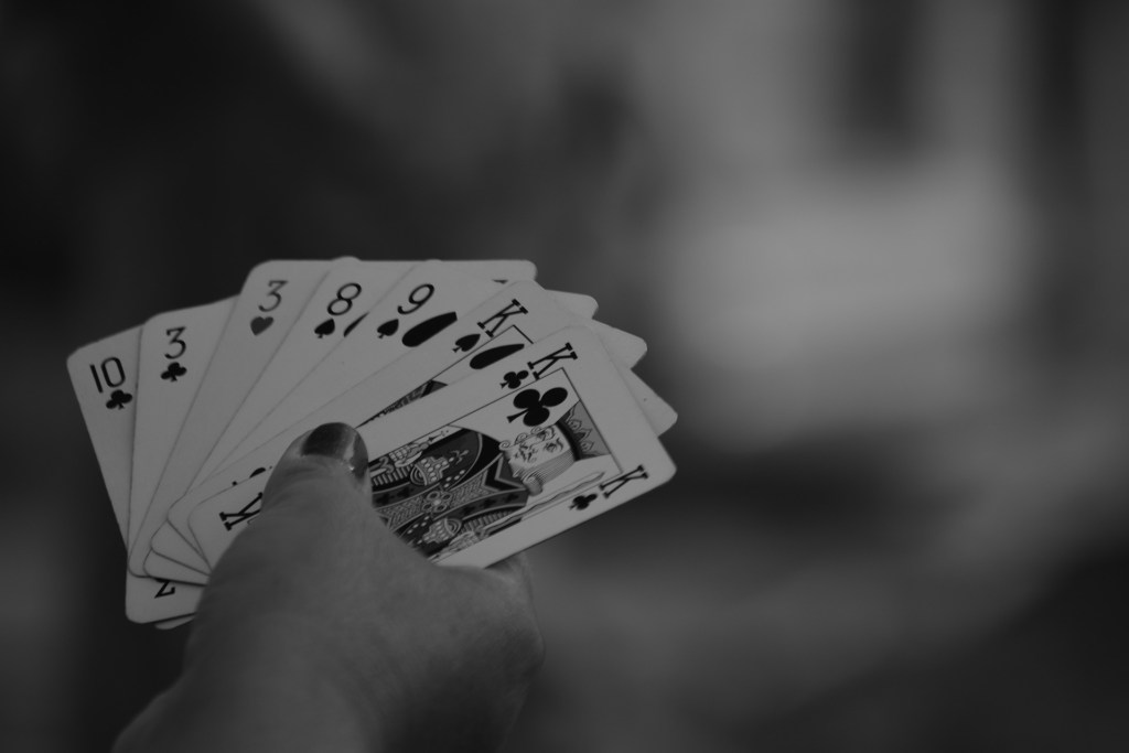 A black and white photo of a woman holding playing cards
