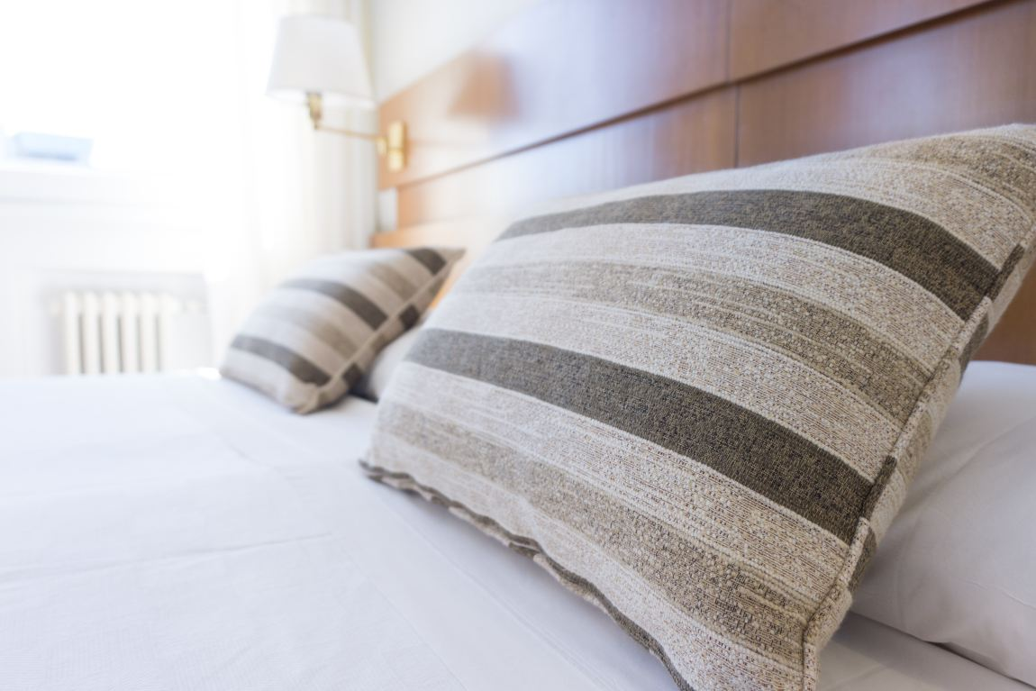 two striped grey cushions sat on a king size bed in a hotel room