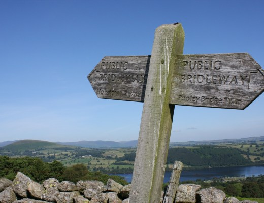 public bridleway signpost in the lake district. Lake Ullswater is in the distance