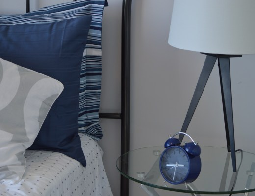 a bed side table with a lamp and blue alarm clock on it next to a bed with a metal headboard