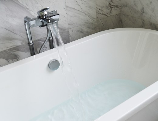 water running into an oval shaped bath - the room has marble effect tiles