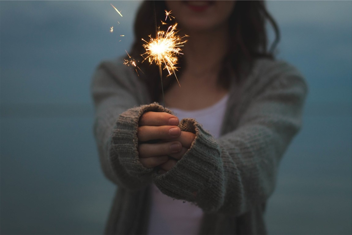 A woman in a light brown cardigan holding a sparkler