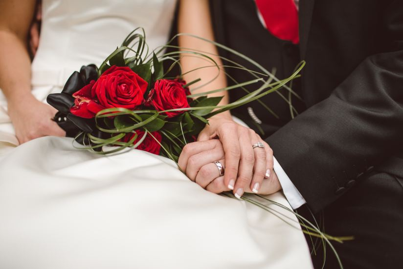 Newly weds showing off their wedding rings, holding hands